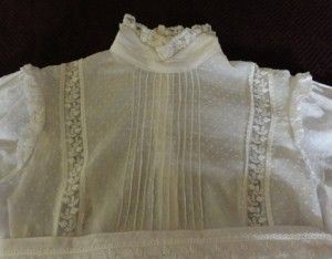 Bodice with pin-tucking, lace panels, and high collar trimmed with lace.