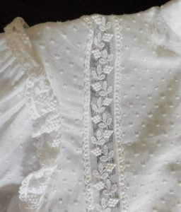 Lace goes over bodice from front waistband to back, and forms a gathered ruffle at top of sleeve.