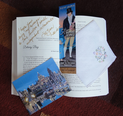 "A Victoria, BC postcard, a bookmark for ""Alias Thomas Bennet"" by Suzan Lauder, and an embroidered handkerchief in honour of the Thrift Shop Regency Costume Experiment are tucked into ""Then Comes Winter"" at Suzan Lauder's ""Delivery Boy"" for the Flat Stanley Book Tour."